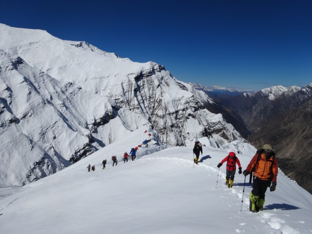 The team stretching their legs after two sedentary days snowed in. Our Pangi ridge camp is in the background.