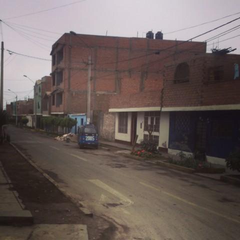 Peruvian street with tuk tuk.