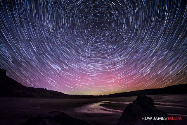 Startrails over Wales with the aurora behind.