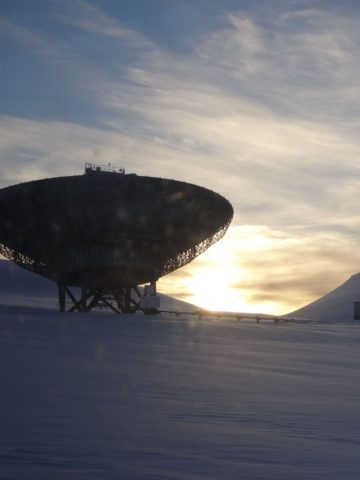 One of the EISCAT radars on Svalbard with the Sun behind, shining on the mountain.