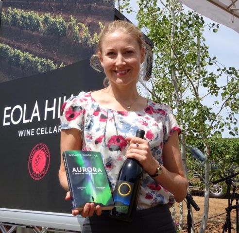 Melanie Windridge at Eola Hills Vineyard with her Aurora book and a bottle of Solar Eclipse pinot noir.