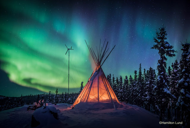 Emerald freeways dance above a tipi fire at Blachford Lake Lodge in Canada's North West Territories.  By Hamilton Lund.