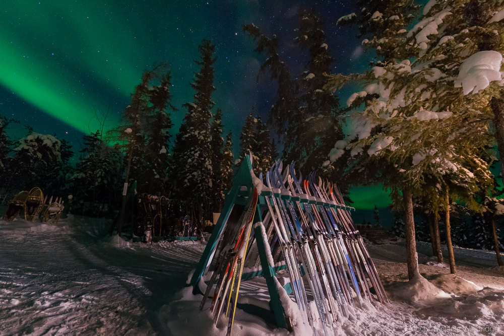 Aurora and skis outside Blachford Lake Lodge, Canada.