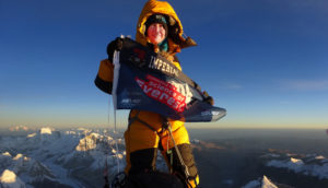 "Melanie Windridge in climbing gear at the summit of Mount Everest, holding a ""science of Everest"" banner"