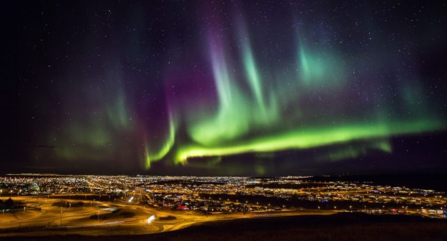 Northern lights dancing over the city of Reykjavik, Iceland.  Credit: The Aurora Zone & Visit Iceland