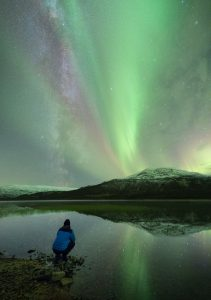 Adrien Mauduit and the night sky with northern lights and stars.