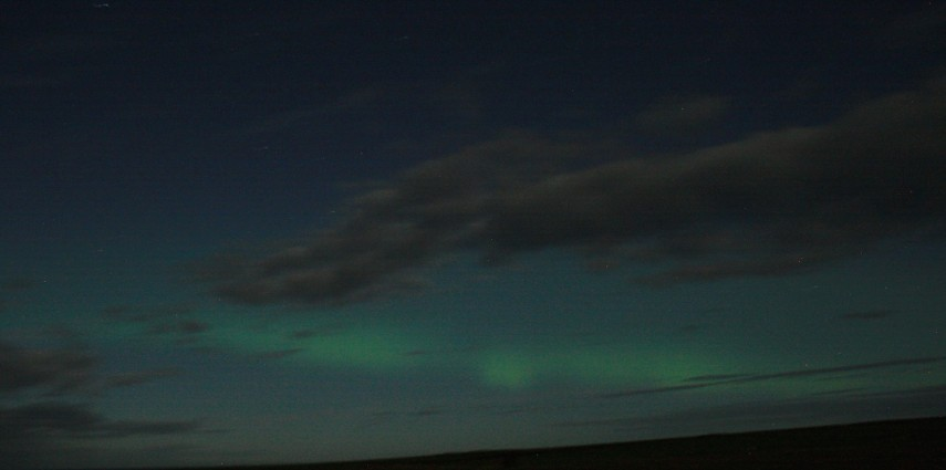 Northern Lights over Orkney on a cloudy, moonlit night.