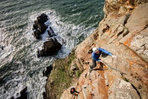 Tom climbing Book of Ages E5 6b at Gogarth. Photo: Dan Lane